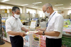 写真=齋藤会長(左)にチラシを渡す加藤支店長