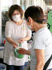 写真=夏のしゅしゅまるまつりで来店客にシトラスリボンを手渡す高階佳津子部長