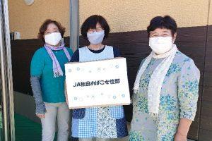 写真=おばここども園の青谷倫子園長(中央)にタオルを寄贈した女性部員